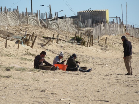 Fishermen hard at work mending baskets of nets.