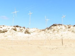 A makeshift wind turbine display on the beach.