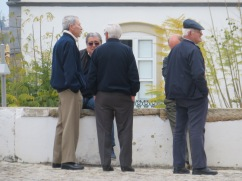 A group of men saying goodbye to one of their friends as a funeral is set to start at the main church in Estoi.