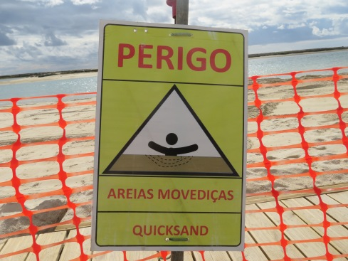 A sign on the beach, completely dug up in places and truck loads of sand piled high in others.