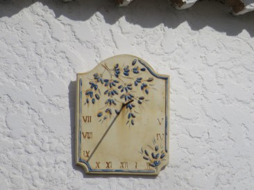 This lovely clock on the upper wall of a quaint old farm house.
