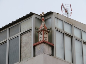A preserved old chimney tucked into a newer building.