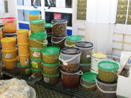 This fellow had an abundance of olives for sale and he was selling loads of them.