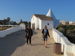 The tiny chapel behind them as they walk out to the point.