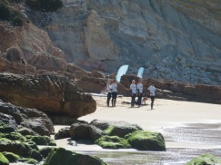 believe this to be a group of new surfers getting a lesson on land before hitting the waves.