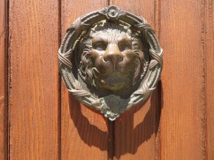 Two enormous identical door knockers adorning these tall wooden doors.