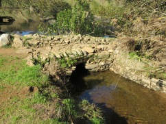 What appeared to be a very old hand made stone bridge over a tributary to the river.