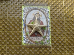 I'm not sure the significance of the starfish which is held on the tile by netting. Perhaps a fisher's house?